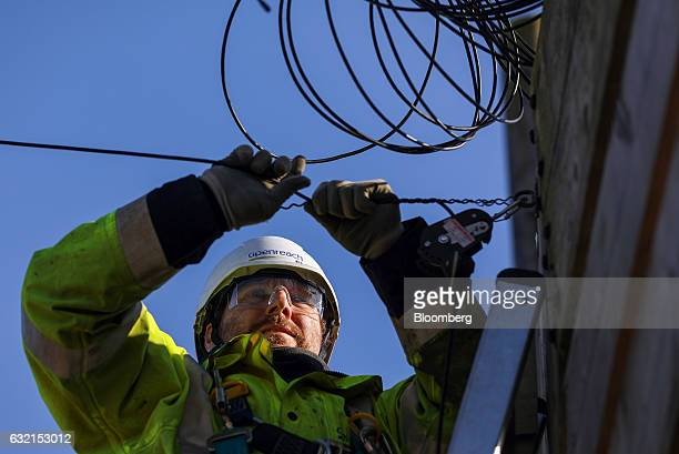 A trainee engineer from BT Openreach a unit of BT Group Plc clamps a wire into position at the top of a telegraph pole at the company's training...
