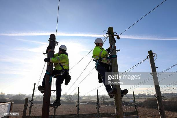 Trainee engineers from BT Openreach a unit of BT Group Plc carry out work at the top of telegraph poles at the company's training facility at West...