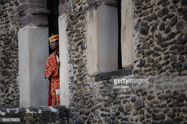 A trainee Ethiopian Orthodox priest looks out from the tower at Fasilides Bath as he awaits the arrival of the Tabot procession during the annual...