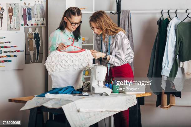 trainee examining dresss fabric by designer holding coathanger at fashion studio - teen russia stock photos and pictures