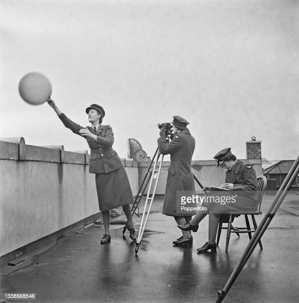Trainee female weather forecaster from the Women's Auxiliary Air Force prepares to release a hydrogen filled pilot weather balloon as two colleagues...