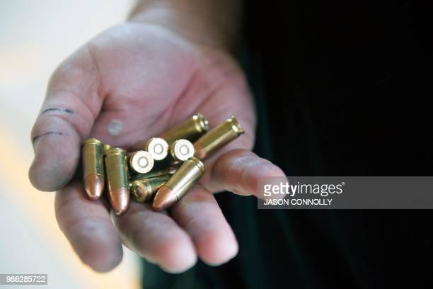 A trainee holds bullets in his hand before reloading a magazine during a threeday firearms training course for teachers and administrators offered by...