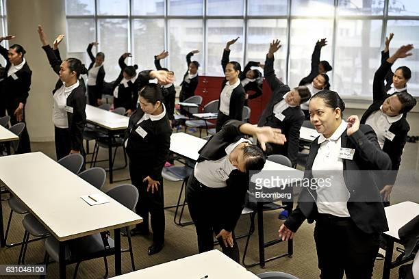 Trainee housekeepers do stretching exercises during a training session at the Magsaysay Center for Hospitality and Culinary Arts, a unit of Magsaysay...