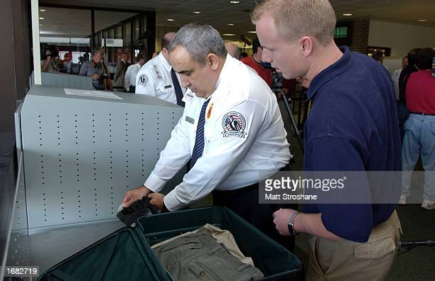 A trainee in the Transportation Security Administration Baggage Screening Training Program examines luggage for trace amounts of explosives under the...