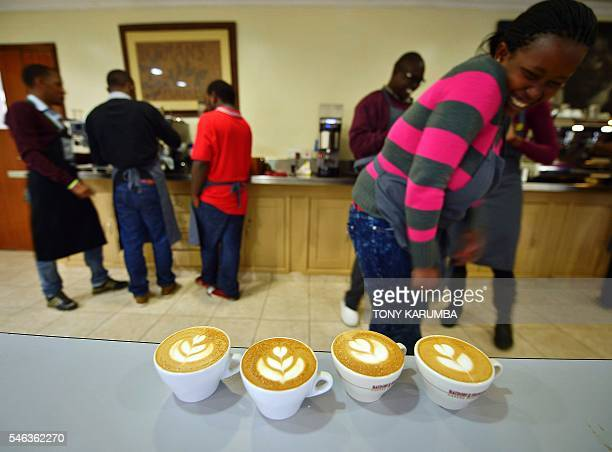 A trainee laugh as she stands behind cups of capuccino with milk decoration commonly known as latte art or coffee art at Dormans cafe in Nairobi on...