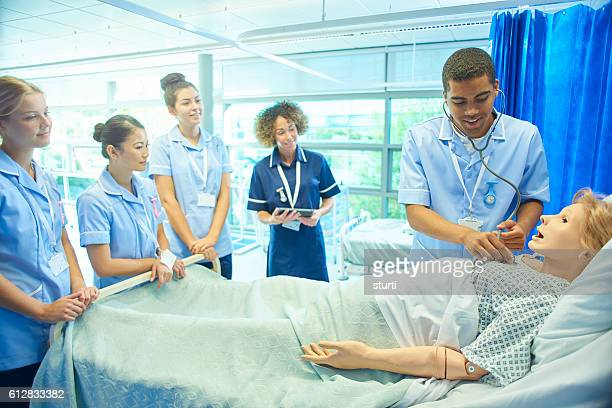 trainee male nurse listening to medical mannequin