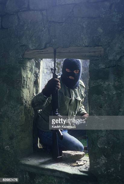 A trainee member of the Provisional Irish Republican Army during an armed assault practice on the ruins of a building at a secret location in the...