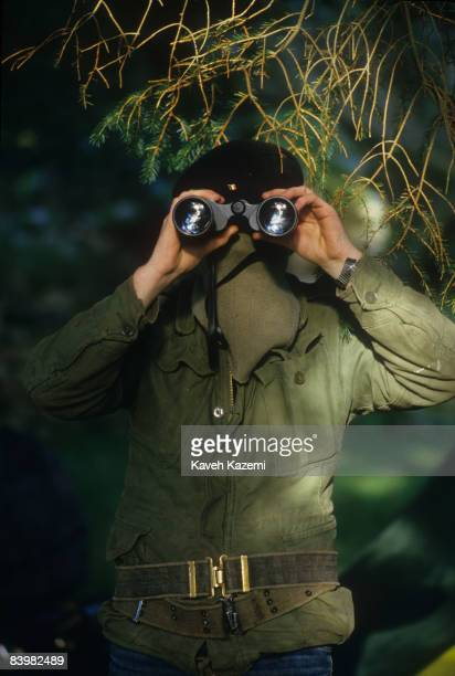 A trainee member of the Provisional Irish Republican Army keeps watch through binoculars while his comrades practice guerilla warfare tactics at a...