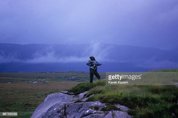 A trainee member of the Provisional Irish Republican Army keeps watch while his comrades practice guerilla warfare tactics at a secret location in...