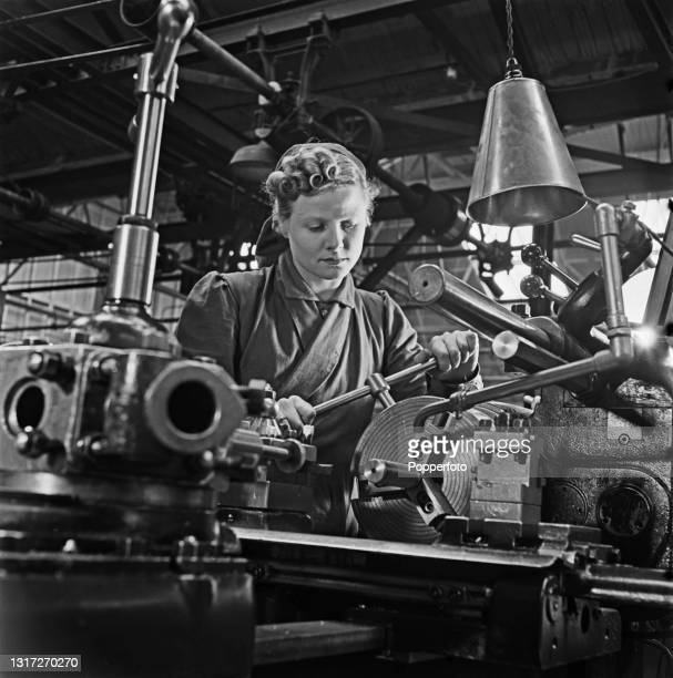 Trainee munitions worker Muriel Maggs, a former cinema usherette, operates a capstan lathe at a British Government training centre in Reading,...
