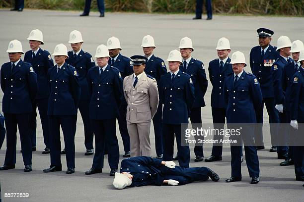 A trainee officer passes out during a parade at a police training school part of the Queen's tour of New Zealand February 1986