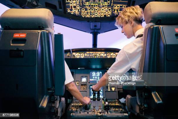 Trainee Pilot Operating Throttle In Flight Simulator With Instructor