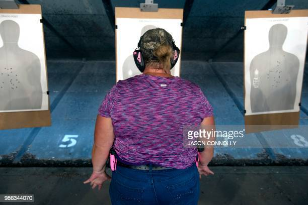 A trainee prepares to fire her gun at a target during a three day firearms training course for school teachers and administrators sponsored by FASTER...