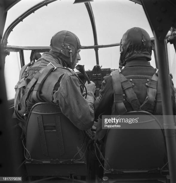Trainee Royal Air Force pupil instructor pilot and instructor seated at the controls in the cockpit of a bomber during a flight above a RAF School...