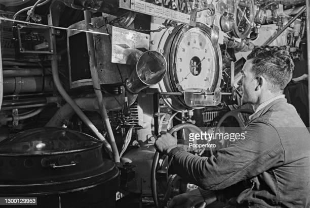 Trainee Royal Navy submariner operates the depth gauge control wheel as part of a training course aboard a submarine at a submarine training school...