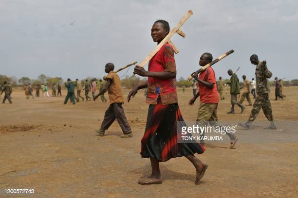 TOPSHOT Trainee soldiers for a new unified army carry their wooden rifles while attending a reconciliation programme run by the United Nations...