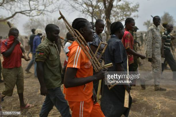 Trainee soldiers for a new unified army carry their wooden rifles while attending a reconciliation programme run by the United Nations Mission in...