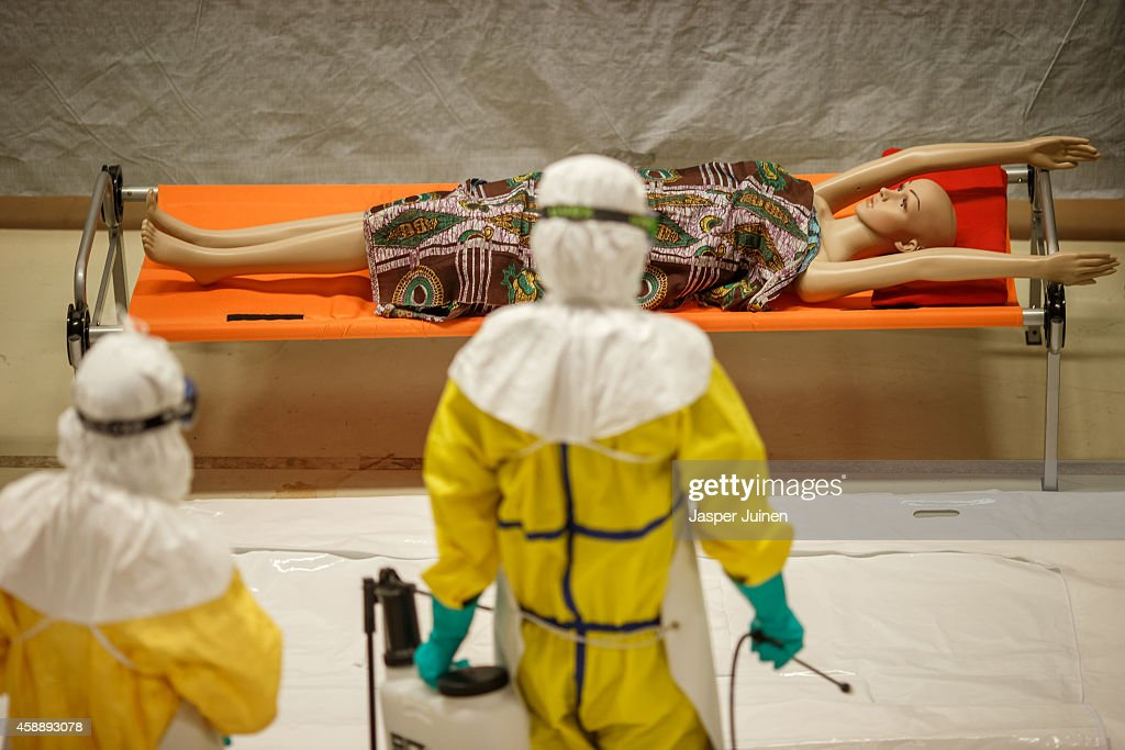 Trainees approach a dummy on a bed during the Ebola training program on November 12, 2014 in Amsterdam, Netherlands. Doctors Without Borders has established a training program in a reproduction field hospital build in an old factory, without electricity and running water, in the Dutch capital for medical personnel world wide who are being sent to countries where Ebola is rife. The charity says it needs hundreds of doctors who are willing and sufficiently skilled to go to Africa to try to help combat the epidemic. The training centre in Amsterdam is the second of its kind after Brussels.