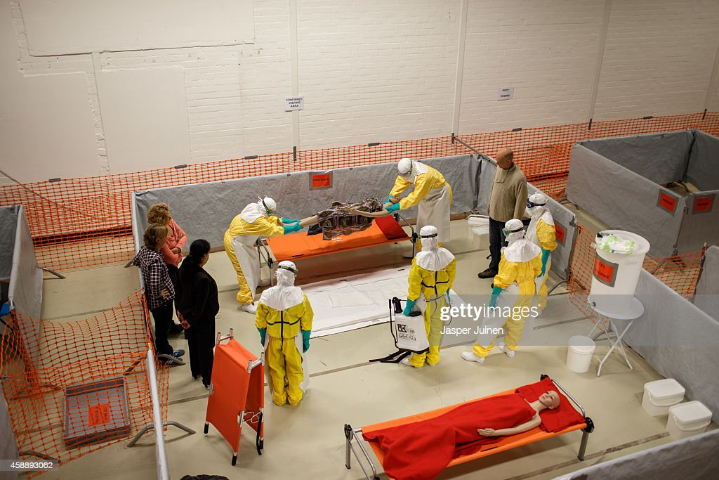 Trainees lift a dummie on a body bag while following the Ebola training program on November 12, 2014 in Amsterdam, Netherlands. Doctors Without Borders has established a training program in a reproduction field hospital build in an old factory, without electricity and running water, in the Dutch capital for medical personnel world wide who are being sent to countries where Ebola is rife. The charity says it needs hundreds of doctors who are willing and sufficiently skilled to go to Africa to try to help combat the epidemic. The training centre in Amsterdam is the second of its kind after Brussels.
