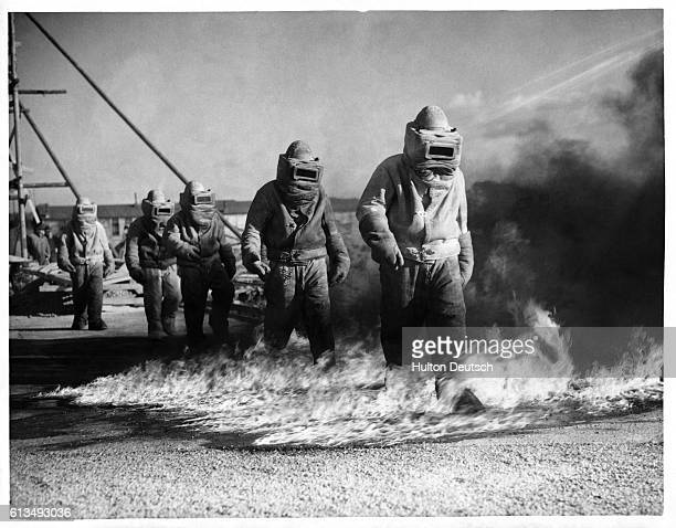 RAF trainees walk through petrol fires as part of their asbestos suit training