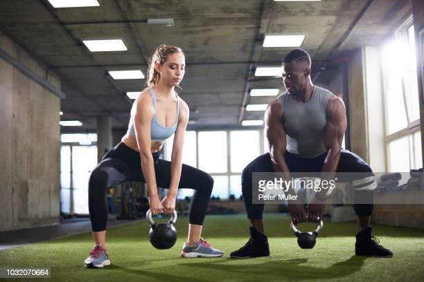 trainer and female client exercise with kettlebells in gym - crouching stock pictures, royalty-free photos & images