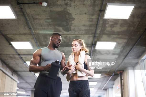 Trainer and female client talking in gym