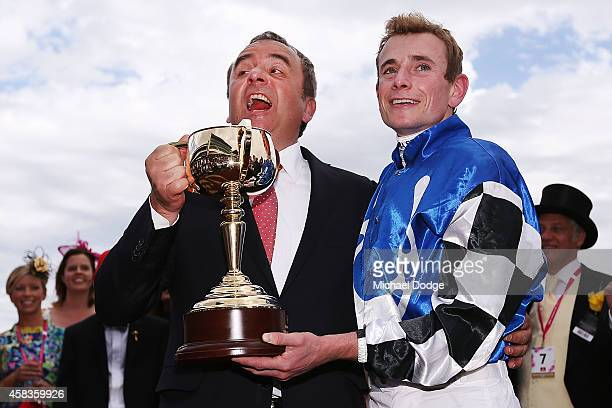 Trainer Andreas Wohler and jockey Ryan Moore celebrate with the trophy after combining to win with Protectionist in race 7 the Emirates Melbourne Cup...