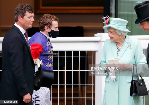 Trainer Andrew Balding and jockey Ryan Moore talk with Queen Elizabeth II in the parade ring before riding her horse 'King's Lynn' in the Wokingham...