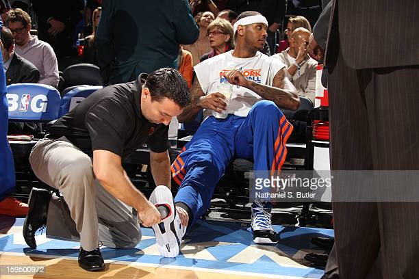 Trainer Anthony Goenaga applies court grip to the sneakers of Carmelo Anthony of the New York Knicks on January 11 2013 at Madison Square Garden in...