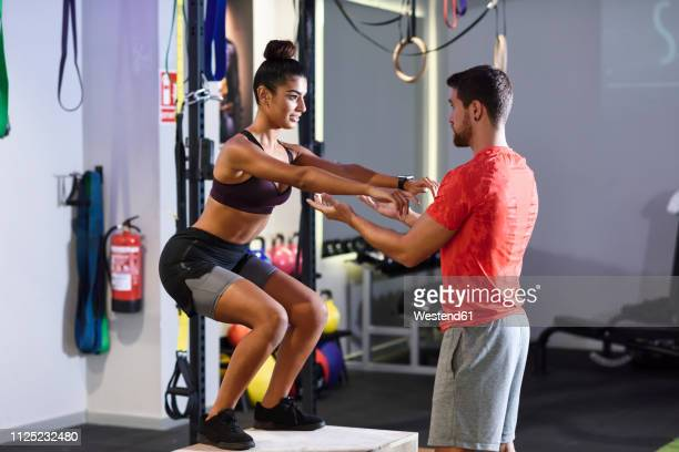 Trainer assisting client, doing box jumps