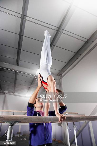trainer assisting gymnast on parallel bars - gymnastics stock pictures, royalty-free photos & images