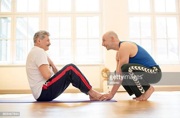 Entrenador hombre ayudando a realizar sit ups