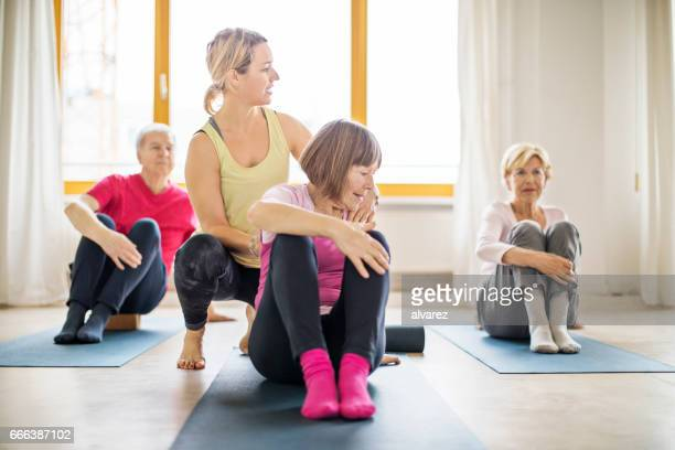 Trainer assisting senior woman in doing yoga