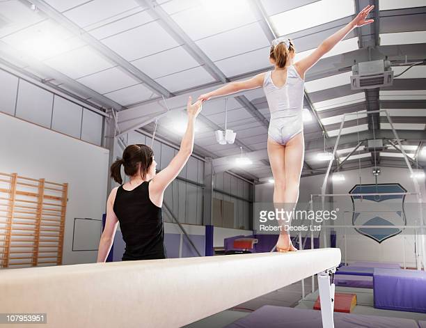 Trainer assisting young female gymnast