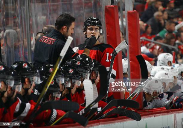 A trainer attends to Nico Hischier of the New Jersey Devils after he was highsticked by Markus Hannikainen of the Columbus Blue Jackets during the...