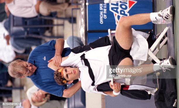 Trainer Bill Norris massages Jerome Golmard's shoulder between games during his second round US Open match against Mark Philippoussis of Australia 27...
