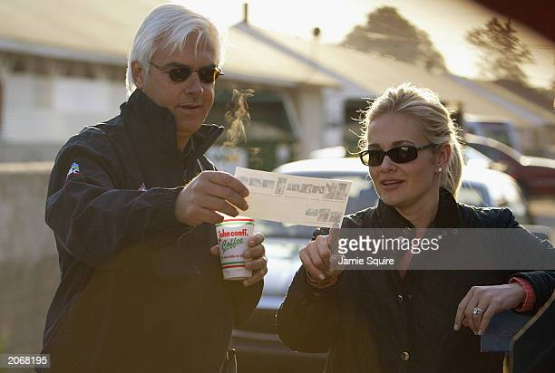 Trainer Bob Baffert and wife Jill look at pictures of their dog during morning workouts for the 129th Kentucky Derby on April 28 2003 at Churchill...