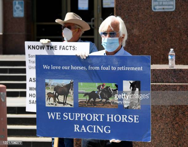 Trainer Bob Baffert holds a sign as he joins horse racing industry workers call to re-open Santa Anita Track in front of the offices of the Board of...