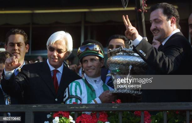 Trainer Bob Baffert jockey Gary Stevens and owner Ahmed bin Salman celebrate with the trophy in the winner's circle after Stevens rode Point Given to...