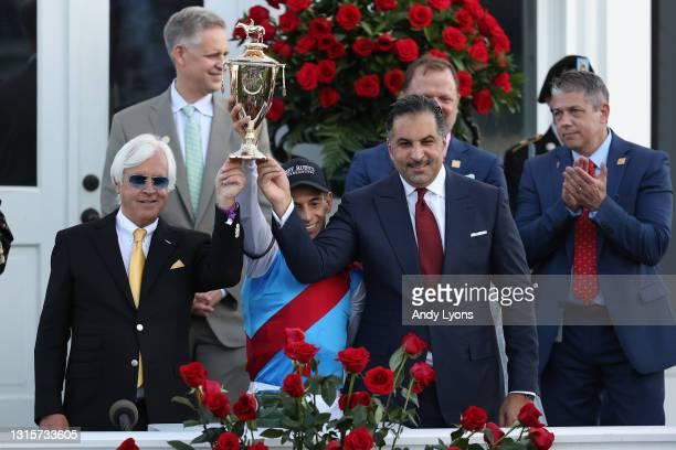 Trainer Bob Baffert, jockey John Velazquez, and owner Amr Zedan of Medina Spirit raise the trophy after winning the 147th running of the Kentucky...