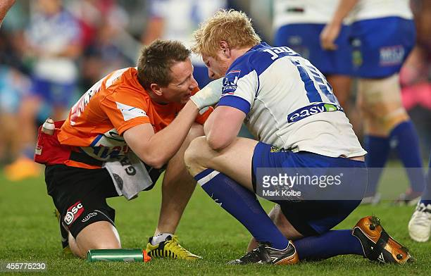 A trainer checks James Graham of the Bulldogs after a heavy tackle during the NRL 2nd Semi Final match between the Manly Sea Eagles and the...