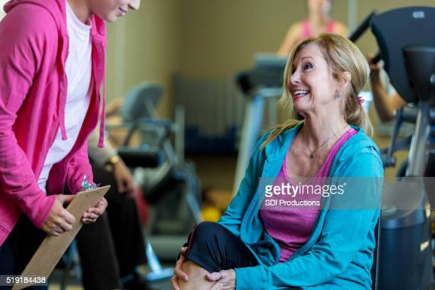 Trainer coaches senior woman in fitness center