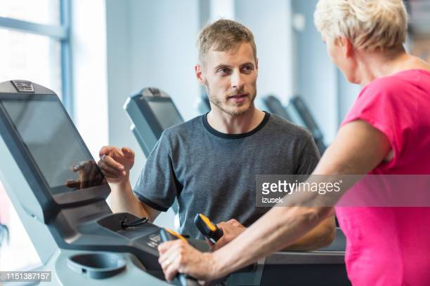 trainer coaching senior woman exercising in rehab gym - drug rehab stock pictures, royalty-free photos & images