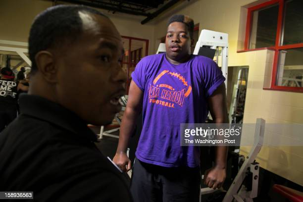 Trainer Daryl Wills helps McDonough High School football player Na'Ty Rodgers with his weight training at the Sport & Health Club in Waldorf,...