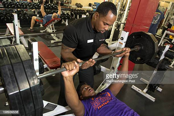 Trainer Daryl Wills spots McDonough High School football player Na'Ty Rodgers on his bench press at the Sport & Health Club in Waldorf, Maryland on...