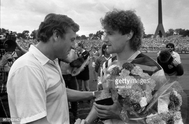 Trainer Eduard Geyer gratuliert am 1281989 im DynamoStadion Dresden dem Spieler Andreas Trautmann von Dynamo Dresden zum 'Silberschuh' für den...