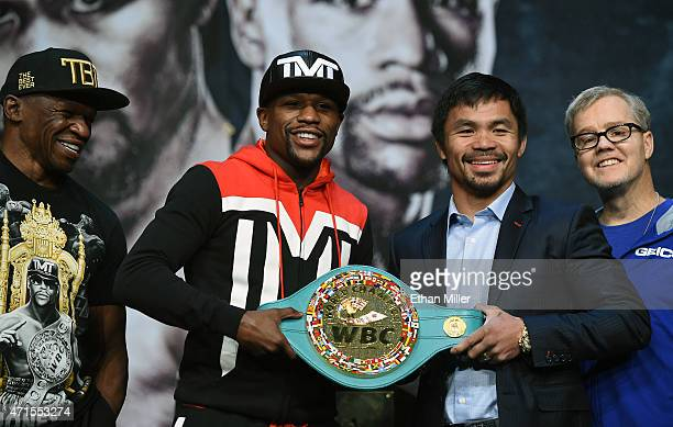 Trainer Floyd Mayweather Sr looks on as WBC/WBA welterweight champion Floyd Mayweather Jr and WBO welterweight champion Manny Pacquiao pose with a...