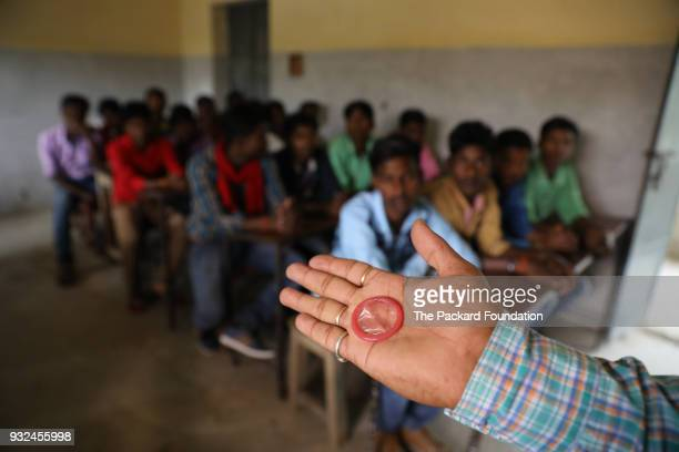 Trainer from Pathfinder International demonstrates condom use for safe sex and pregnancy prevention to adolescent boys at the village school. These...