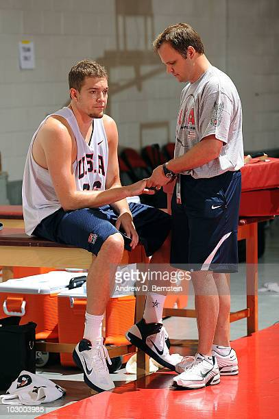 Trainer Gregg Farnam attends to David Lee of the 2010 USA Basketball Men's National Team after he suffers from a right middle finger injury during...