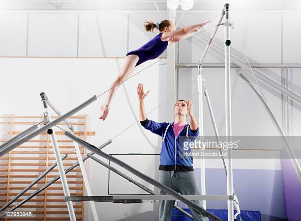 trainer guiding  young gymnast on parallel bars - gymnastics stock pictures, royalty-free photos & images